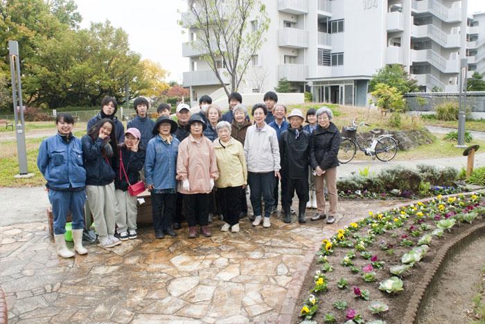完成した花壇の前で。「毎日の世話は大変なこともあるけれど、喜びも多い。ぜひボランティアに参加してもらえたら。」と馬坂自治会長。